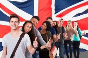 student posing with the Union jack flag with a thumbs up
